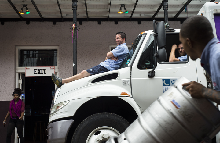 Shavonne Butler stands outside the Krazy Korner, the bar where she MCs, while Bo Bordelon (left to right) and Chris Howard relax with their truck as it is unloaded on Bourbon Street.