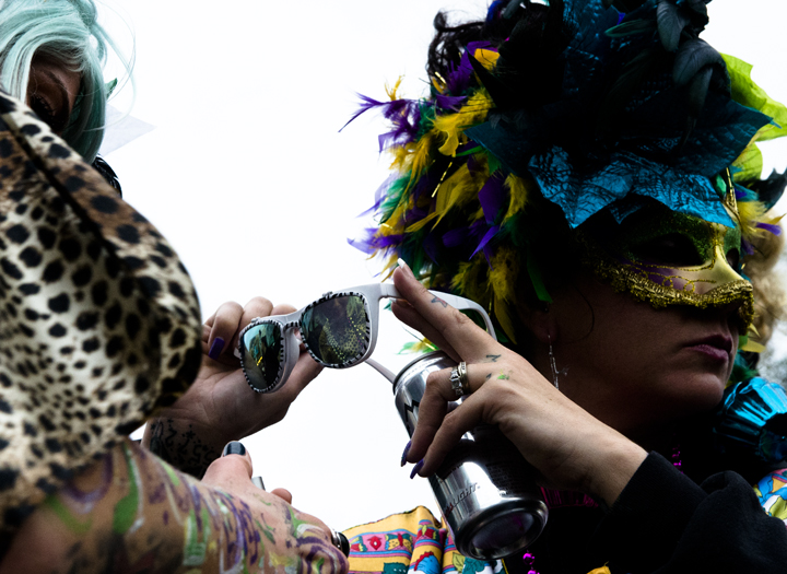 Lindsay Lew, right, holds up glasses so Lissa Lenis can check her lipstick while they take a break from dancing at the Zulu Festival.