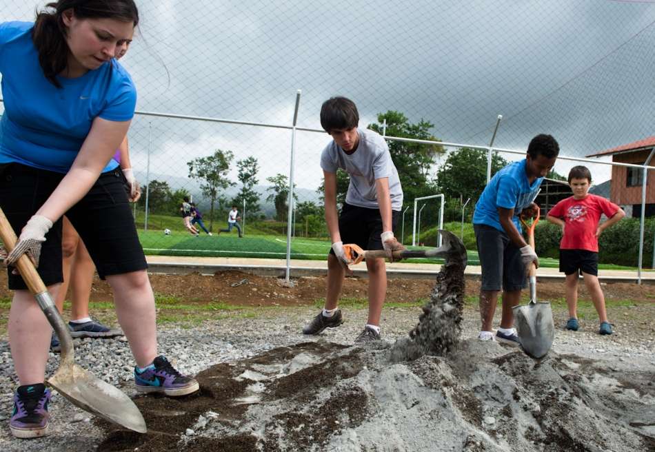 Peyton, Zane and Brandon mix cement for the floor of a storage area while our friend Hector watches.